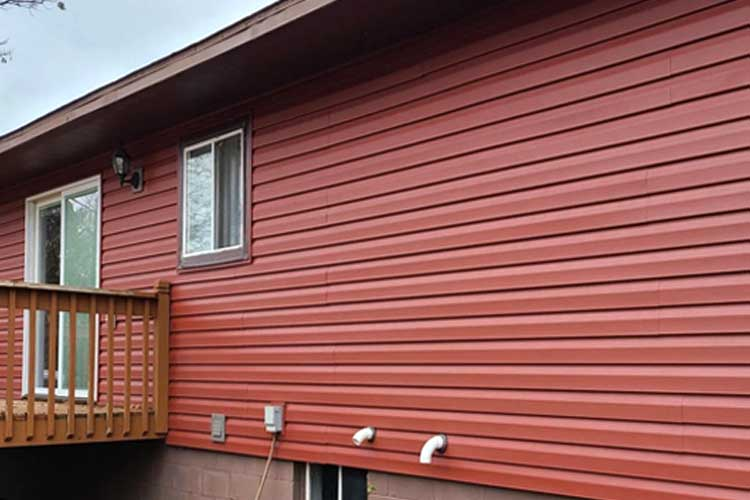 Photo of beautiful, brick-colored, new steel siding on house